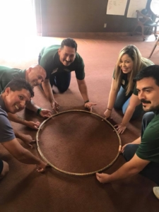 Picture of team-building exercise with hoop.